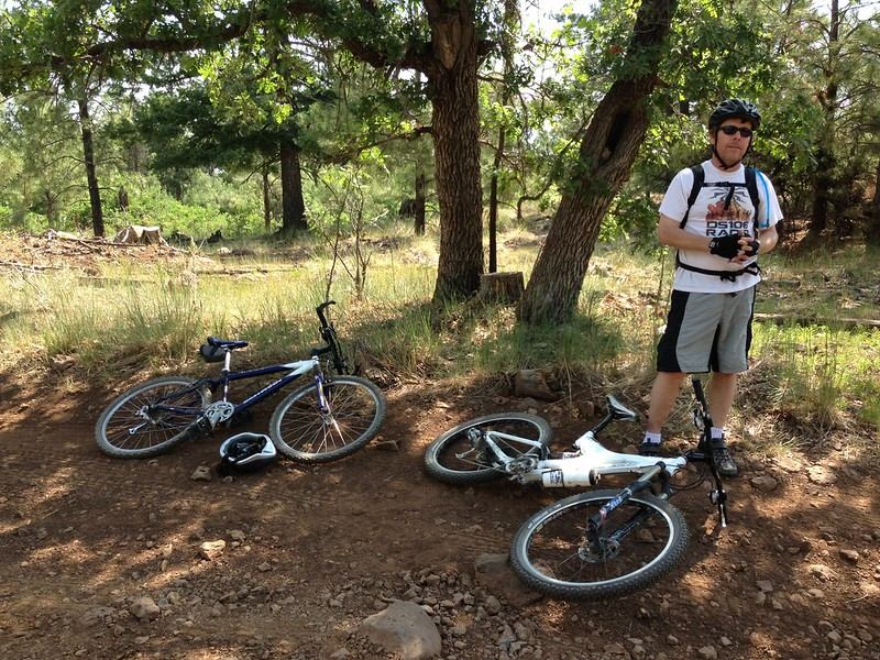 A guy named Todd in bike gear, under a tree, stands next to 2 bikes on ground.